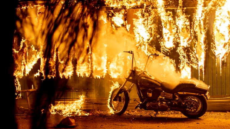 A structure and a motorcycle burn at an RV park during the Woolsey Fire in Malibu